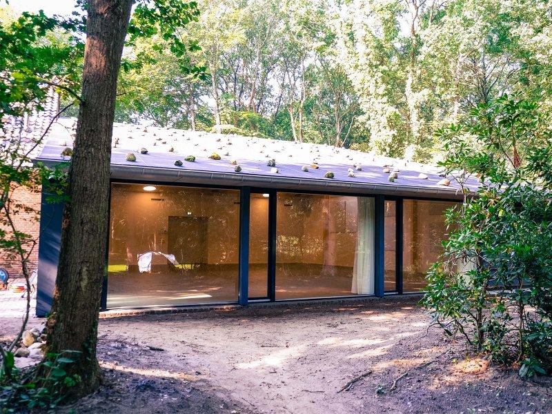 De glazen pui aan de achterkant van de nieuwe zaal laat het groen van het omringende bos toe